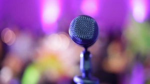 microphone-on-a-stage-with-blurred-audience-in-front-taken-from-stage_vyvmezczg__F0000